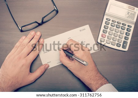 Man writing a check on his desktop viewed from above - stock photo