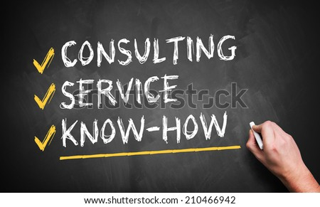 man writing consulting, service, know how on a blackboard - stock photo