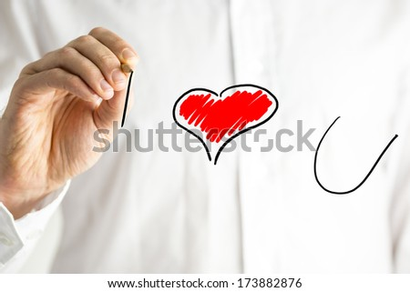 Man writing I Love You on a virtual screen with a red heart symbolising the word love as he declares his feelings for a loved one or sweetheart on Valentines Day or a special occasion - stock photo