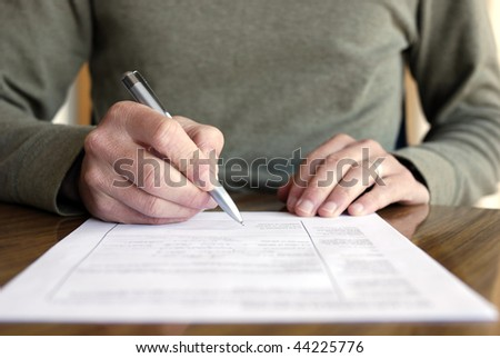 Man writing on paper with pen on table.  Horizontally framed shot. - stock photo