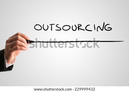 Man writing the word Outsourcing with a black marker pen from behind a virtual screen or interface on a light grey background with copyspace.