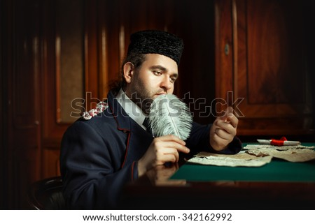 Man wrote the manuscript with a quill pen in retro style. It retro form last time. The manuscript is not legible handwriting. - stock photo