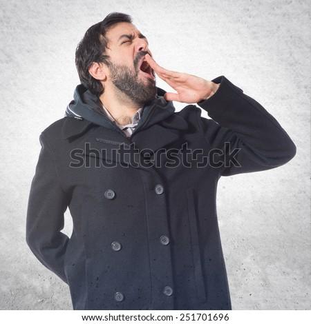 Man yawning over textured background - stock photo