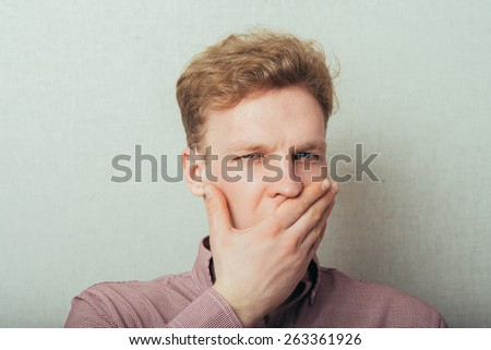 man yawns, covering her mouth - stock photo