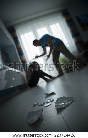 Man yelling at woman on the floor - stock photo
