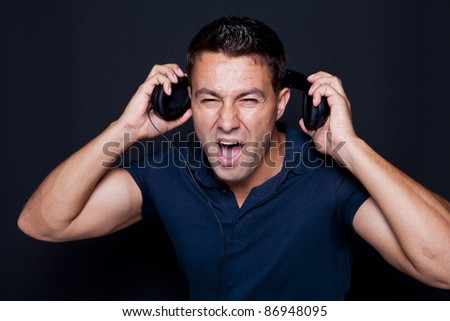 Man yelling while listening to headphones in black background - stock photo