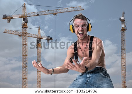 man yells at the background of cranes, lifting something up - stock photo