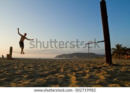 MANABI, ECUADOR - JUNE 5, 2012: Unidentified young man balancing on slackline at a beach in Manabi. - stock photo