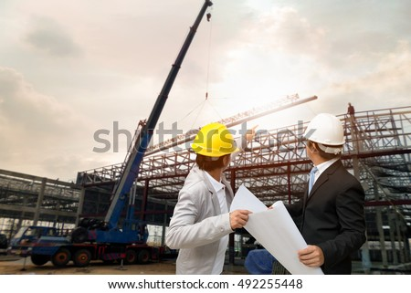 Management consulting engineers working hard hat stock photo management consulting with engineers working with hard hat and holding blueprint in his hand for management malvernweather Choice Image