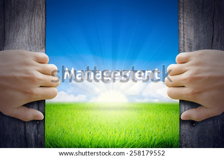 Management. Hand opening an old wooden door and found Management word floating over green field and bright blue Sky Sunrise. - stock photo