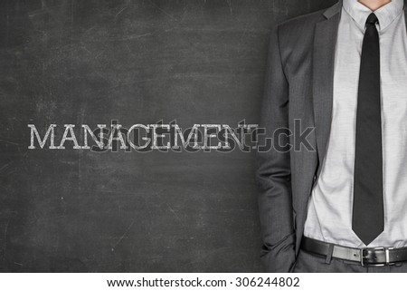 Management on blackboard with businessman in a suit on side