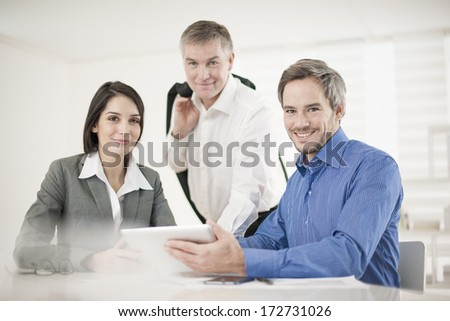 manager and his workteam at office looking at camera - stock photo