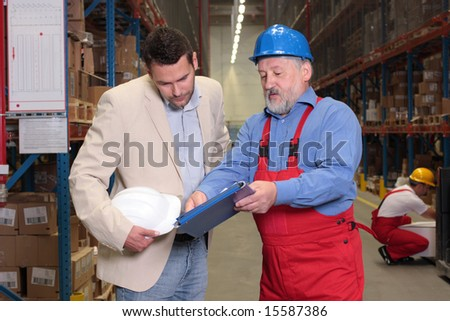 manager and older worker talking over papers in warehouse - stock photo