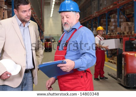 manager and older worker talking over papers in warhouse - stock photo