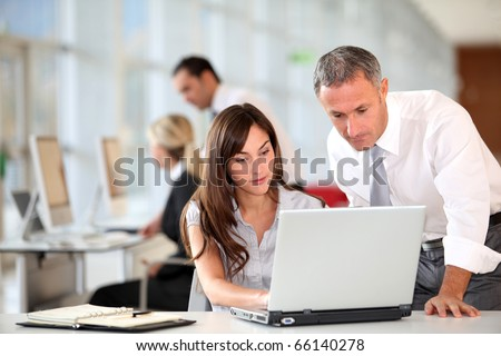 Manager and secretary working in the office - stock photo