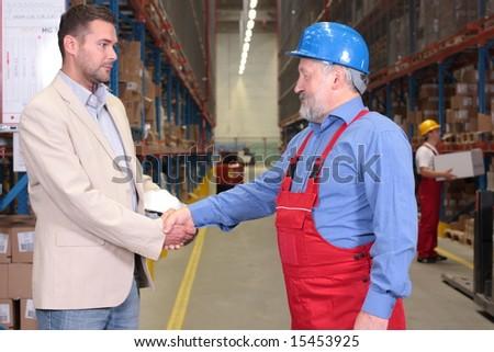 manager and senior worker handshake in warehouse - stock photo