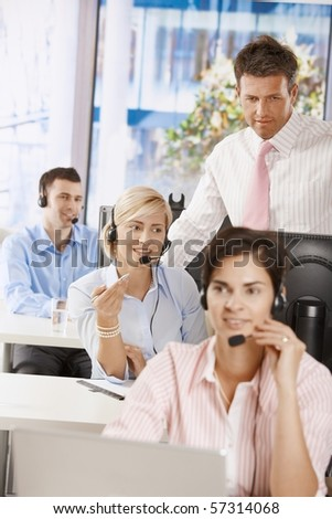 Manager checking customer service operators in office.? - stock photo