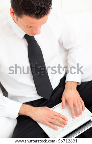 Manager checking mails in hotel on bed couch