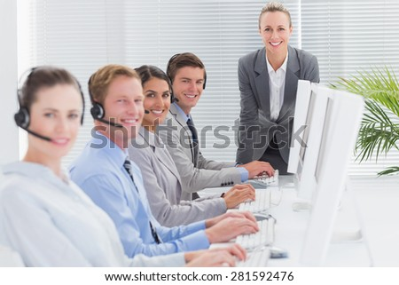 Manager checking the work of the staff in call center - stock photo