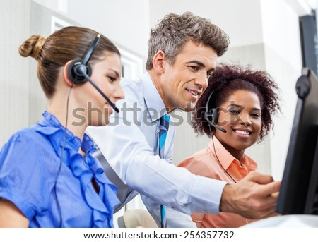 Manager explaining something to his employees in call center - stock photo