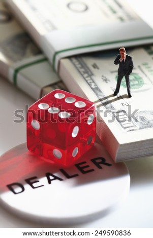 Manager figurine standing on bundle of 100 us dollar notes with dice - stock photo