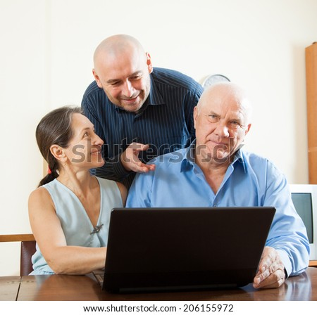 Manager helping to senior couple with laptop