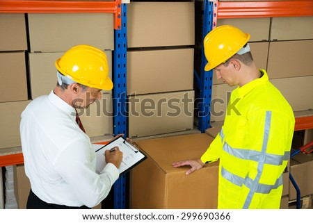 Manager Holding Clipboard Checking The Inventory With Warehouse Worker - stock photo