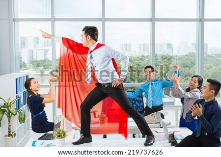 Manager in a red cape posing in front of his colleagues - stock photo