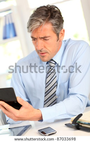 Manager in office calculating budget - stock photo