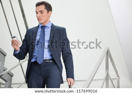 Manager in staircase looking for network coverage with his smartphone - stock photo