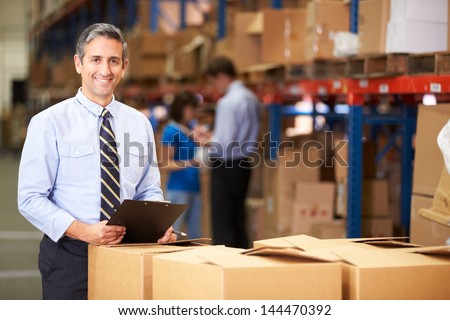 Manager In Warehouse Checking Boxes - stock photo