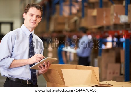 Manager In Warehouse Checking Boxes Using Digital Tablet - stock photo