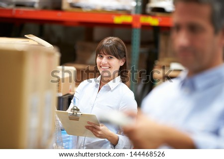 Manager In Warehouse With Worker Scanning Box In Foreground