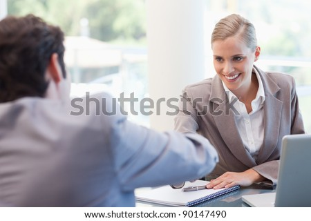 Manager interviewing a male applicant in her office - stock photo