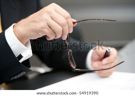 manager keeps his eyeglasses in his right hand during the negotiation