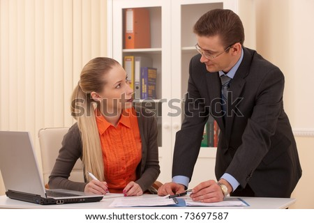 manager man and his secretary working together in the office - stock photo