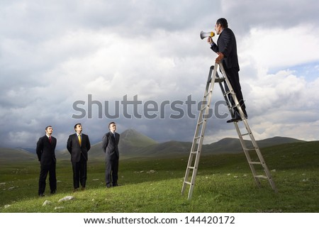 Manager on ladder speaking through megaphone to businessmen in mountain field - stock photo