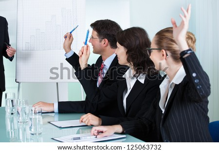 Manager or senior business executive standing in front of a graph giving a presentation to staff or colleagues seated at a table - stock photo