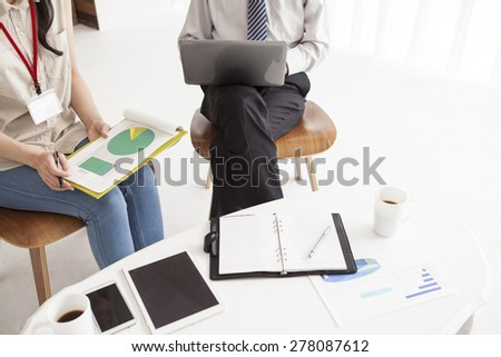 Manager pointing at something to her employee on a graph in his office - stock photo