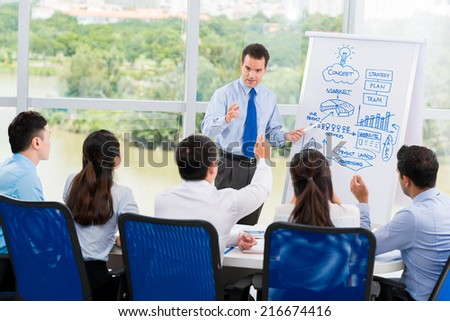 Manager presenting new business strategy to his employees - stock photo