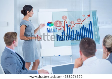 Manager presenting statistics to her colleagues against graph - stock photo