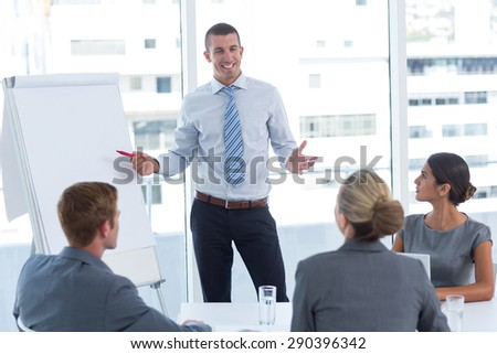 Manager presenting whiteboard to his colleagues in the office - stock photo