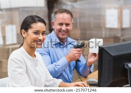 Manager scanning box while his colleague typing on laptop in a large warehouse - stock photo
