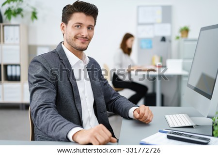 manager sitting at desk and working on computer with co-worker in background