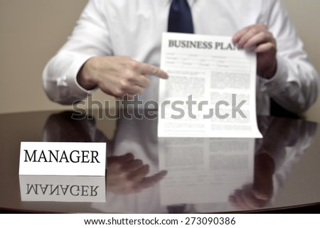 Manager sitting at desk holding Business Plan document for deal