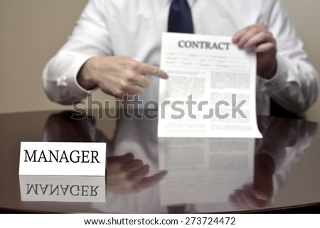 Manager sitting at desk holding Contract document for deal  - stock photo