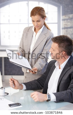 Manager sitting at desk, secretary bringing contract to sign.