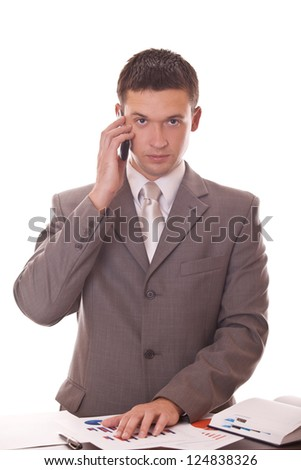 manager talking on phone while standing near table with documents