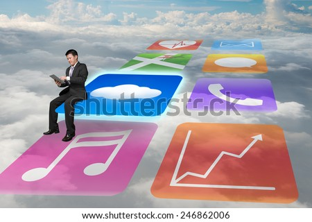 Manager using tablet sitting on shiny cloud app icons with cloudscape background - stock photo
