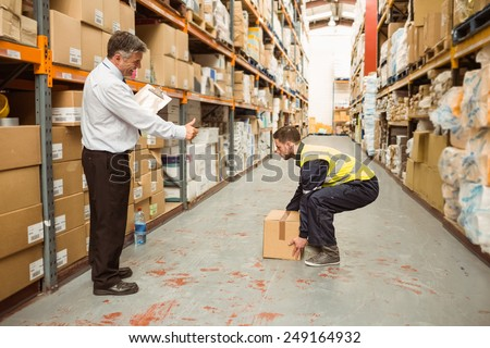 Manager watching worker carrying boxes in a large warehouse - stock photo